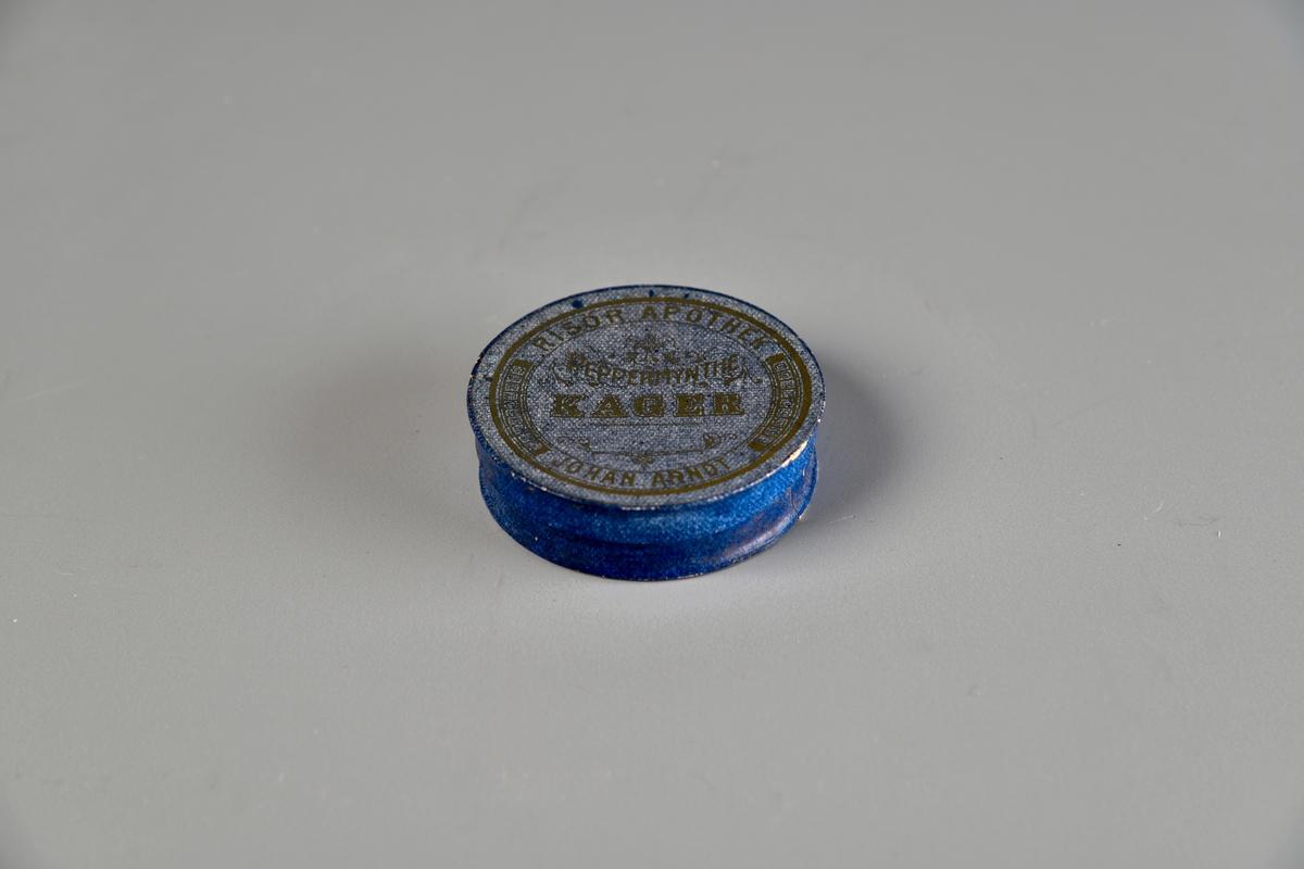 Rund pappeske med lokk som kan tas helt av. Hvit på innsiden. Firmalogo og apotekerens navn trykket på lokket, samt dens innhold.
