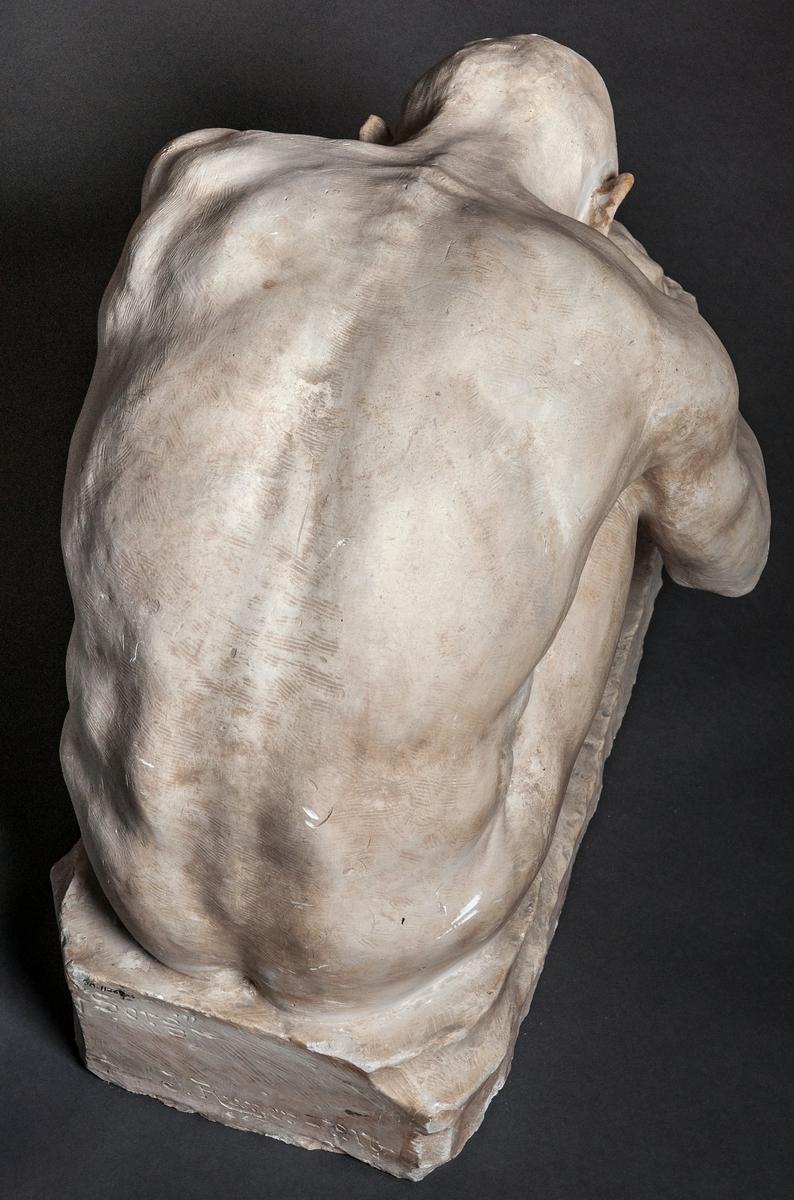 """Skulptur i gips, detalj av gravmonument, kallad """"Sorg"""", av John Runer. Återger en man naken sittande på marken, med huvudet ner mellan knäna."""