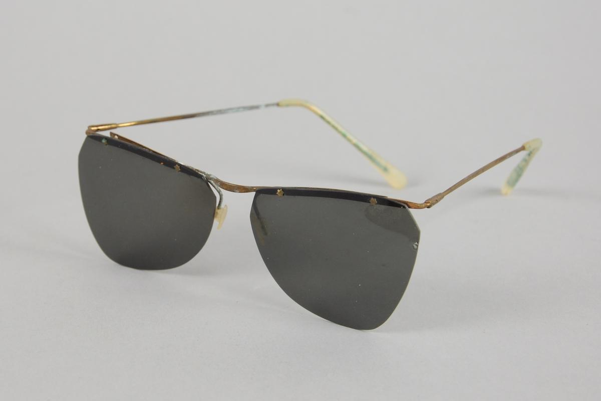 Solbriller uten innfatning og med billestenger av metall og kledd med plast ytterst.