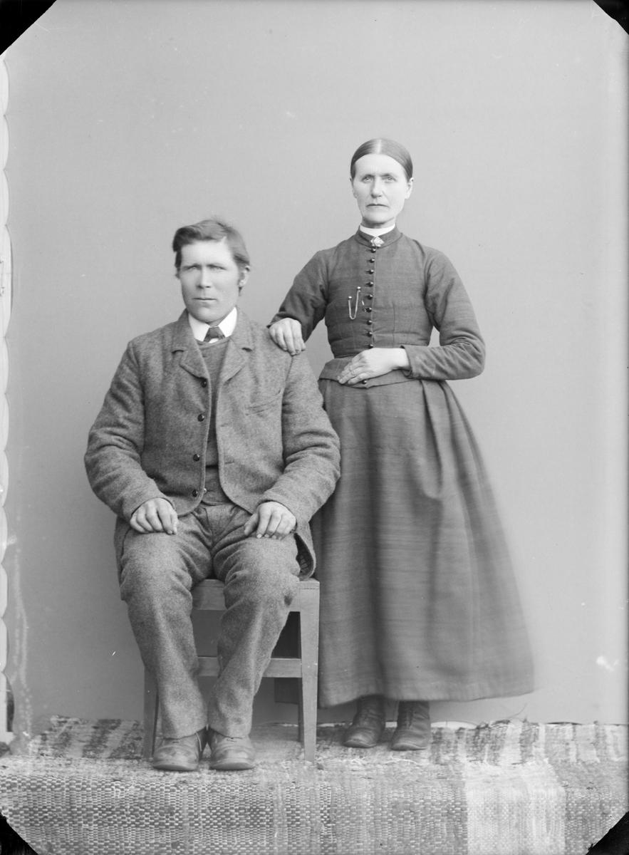 Mann med vadmelsdress og dame med sid stakk, muligens ektefeller.