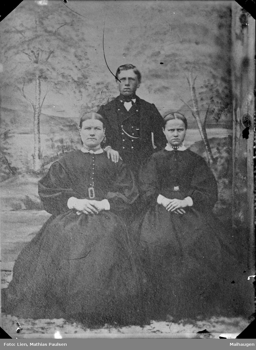 Repro av eldre bilde med to damer og en mann, atelierbakgrunn. Samme motiv på MPL-0323.