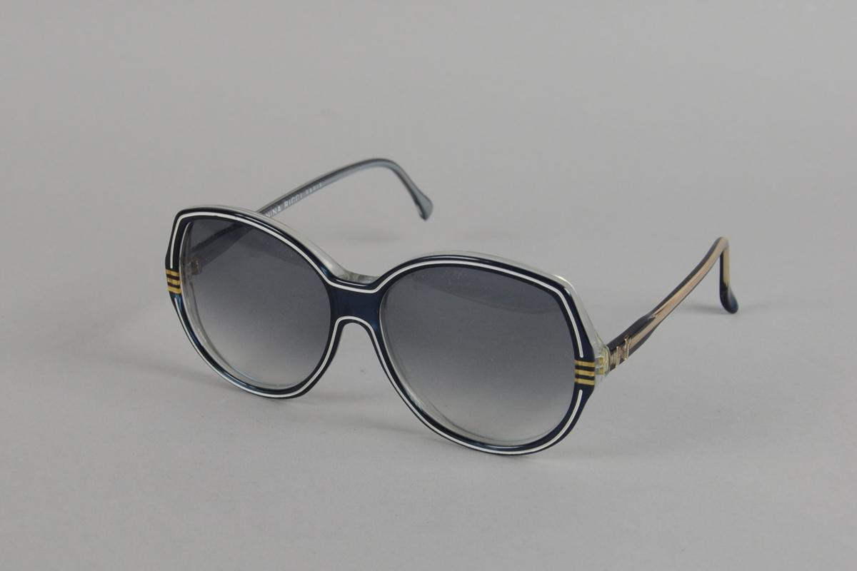 Store runde solbriller (Nina Ricci, Roma) av blå plast med hvit stripe på innfatningen. Stangen har påsatt N og en blank stripe. Brillene har farget glass. De ligger i et sølvfarget etui av tekstilt materiale.
