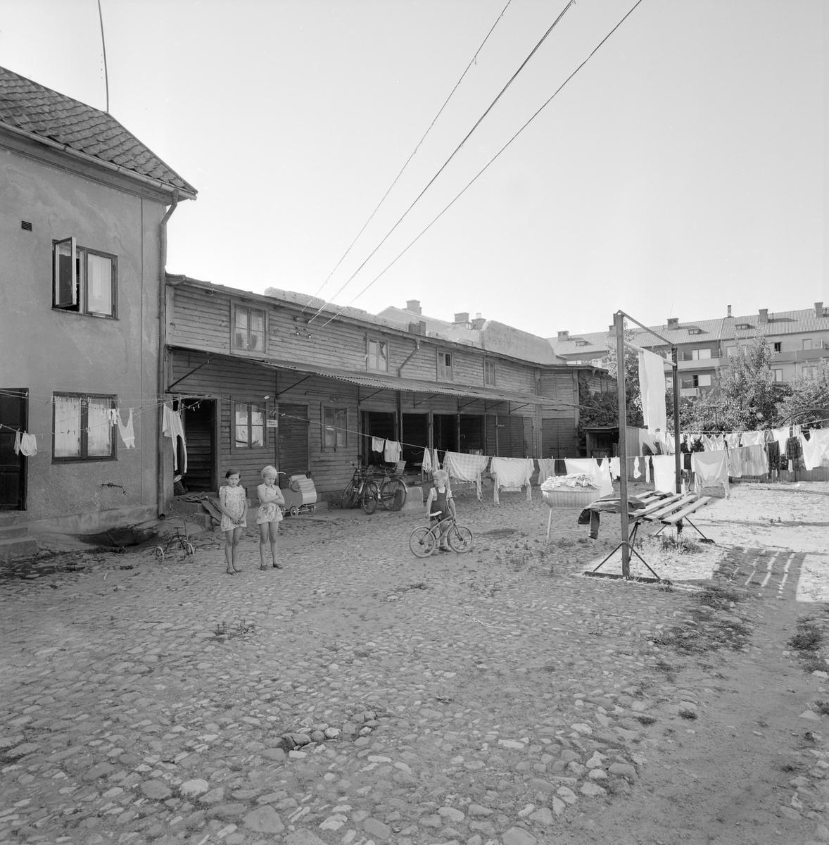 Gårsdsinteriör från Storgatan 7 i Linköping. Likt de flesta innergårdar i staden en egen värld med plats för åtskilligt. Året är 1956.