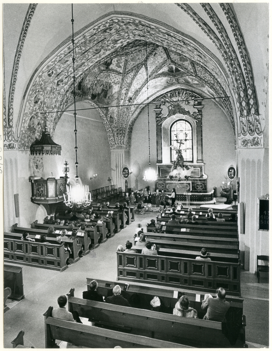 Dingtuna sn, kyrkan.  Gudstjänst i Dingtuna kyrka. Åhörarna sitter i kyrkbänkarna och en grupp barn står vid altaret.