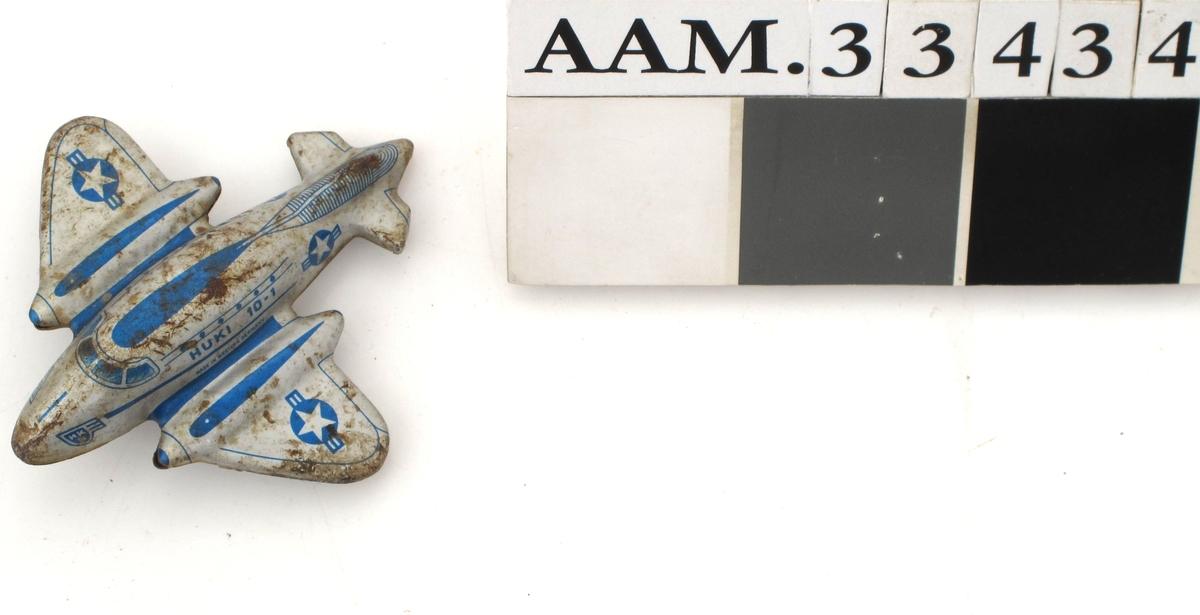 Lekefly av metall, satt sammen av to hoveddeler, utstanset og presset i form, overside og underside som er montert sammen. Grå og blå farge.  Stjerne og striper.  US Air Forse.