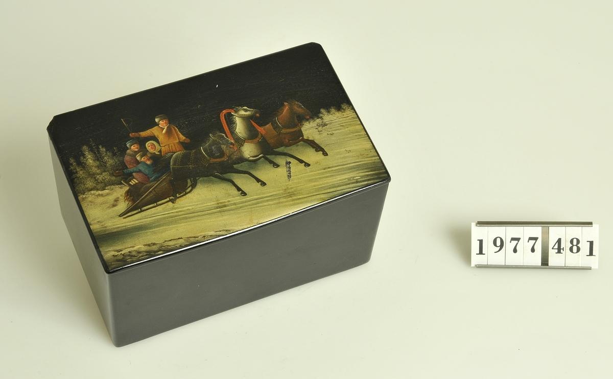 Med lock. Rektangulär form. Locket fäst på gångjärn av mässing. Målning på locket: Vinterlandskap med släde förspänd med tre hästar i bredd.