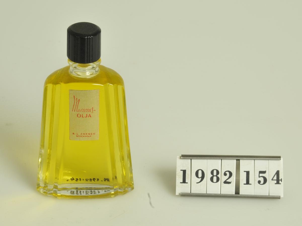 """Innehållande hårolja:: macassarolja.  Märkt: """"Macassarolja AB Eresco"""".  Ofärgad flaska med skruvhatt av svart bakelit.  Håroljans färg: gul.  Storlek: 10 cm hög.               5,5 cm bottens bredd (flaskan avsmalnande upptill.)  Flaskan funnen i källaren till fastigheten kv. Cederberg 3 (f.d. Andréns tobaksaffär.)"""