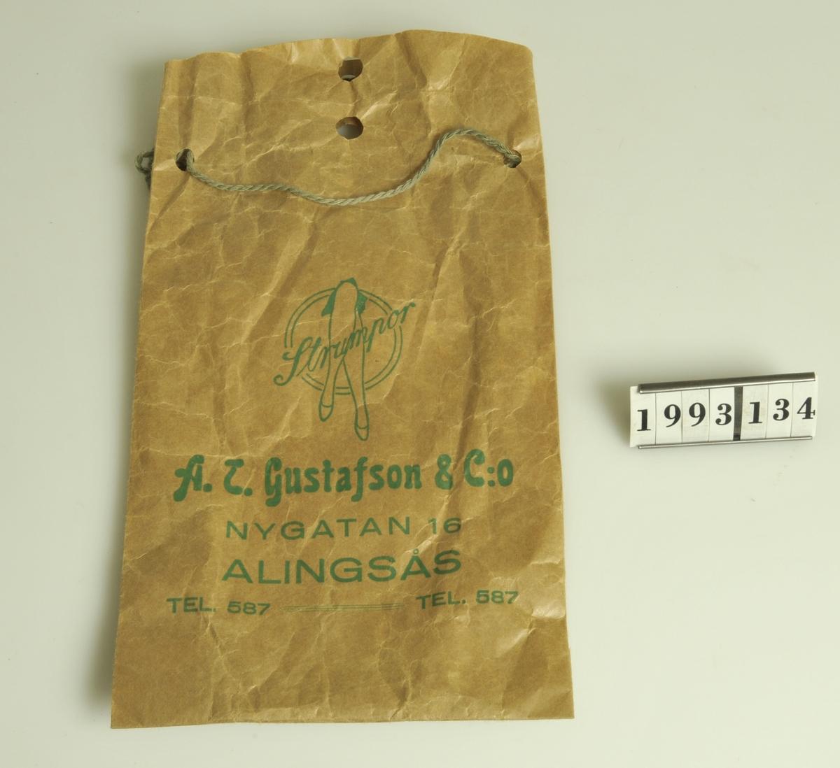 Grön. Grön text: Strumpor A.T. Gustafsson & Co Nygatan 16  Alingsås