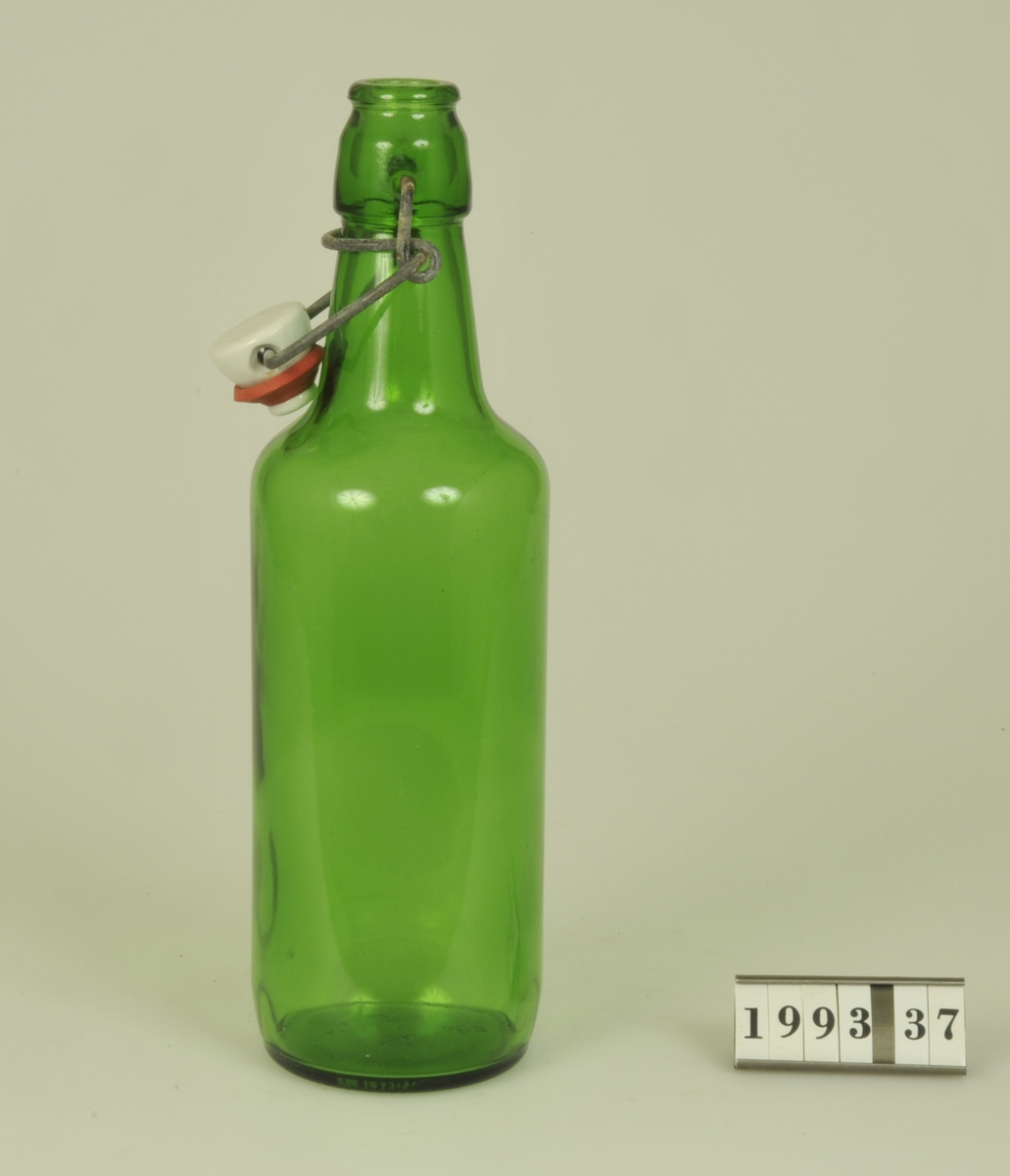 Grönt glas, vit porslinskapsyl och gummiring. I botten märkt: IMB 0,5 L
