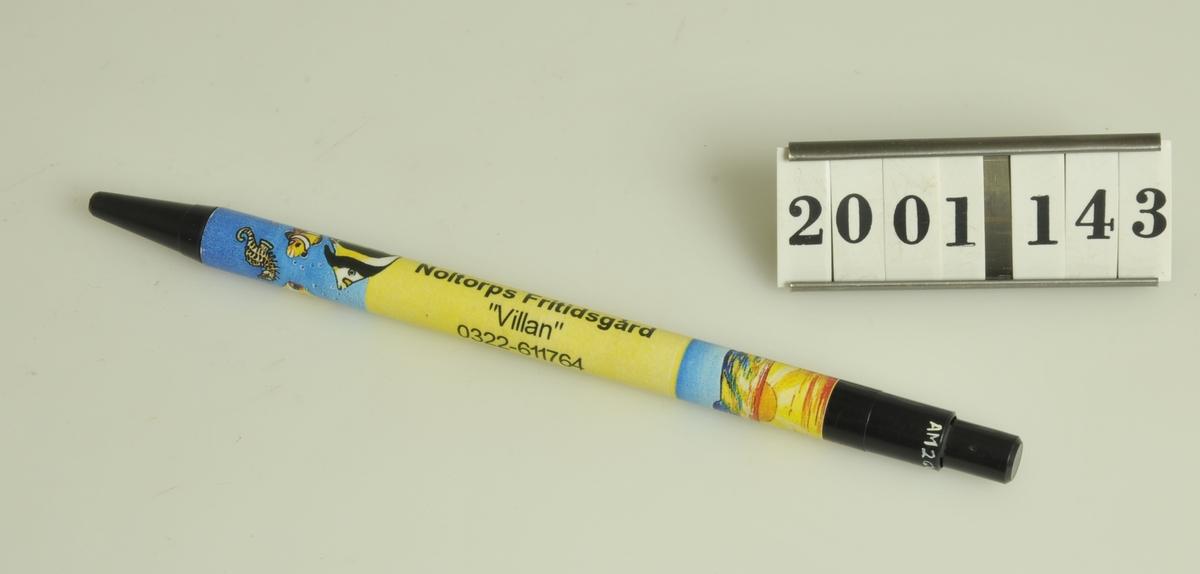 """Pennan har svarta ändar, mitten är gul med solnedgångs- och fiskmotiv. Försedd med texten:: Noltorps fritidsgård """"Villan"""" 0322-61 17 64  ALINGSÅS. Tillvaratagen av museets personal."""