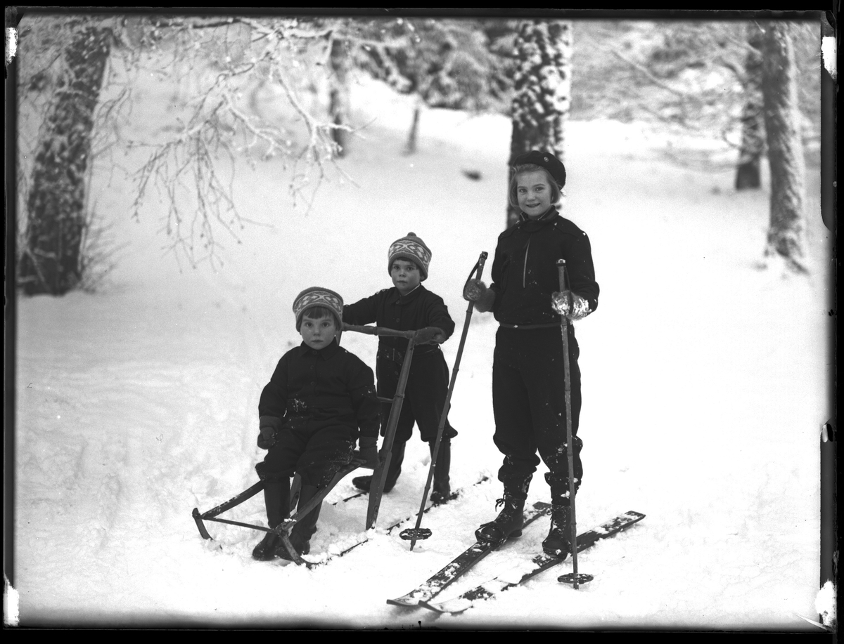 """En flicka står på ett par skidor. Hennes yngre bror sitter på en kälke medan hans tvillingsyster står bakom och puttar på. I fotografens anteckningar står det """"Ing.[enjör] Bergs barn"""", tolkat som tvillingarna Peter Wilhelm och Ulla Maria samt deras storasyster Elsa Margareta."""