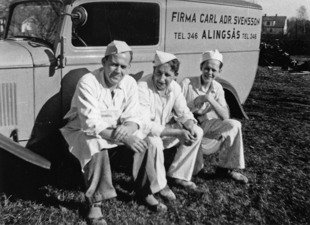 3 män sitter på fotsteget till firmabilen till Firma Carl Adrian Svensson tel. 346. Firman var partiaffär i mjöl, socker, bensin, fodervaror och oljor och låg i kv Jägaren 11, Kungsgatan 38.