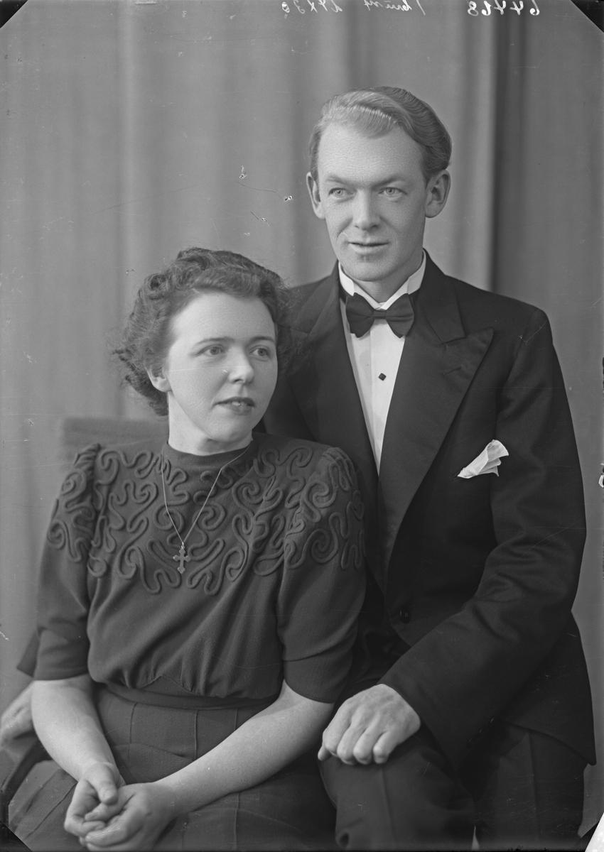 Portrett. Ung kvinne i mørk kjole med brodert mønster i front og ung mann med mørk dress med mørk sløyfe. Bestilt av Sverre Lie.