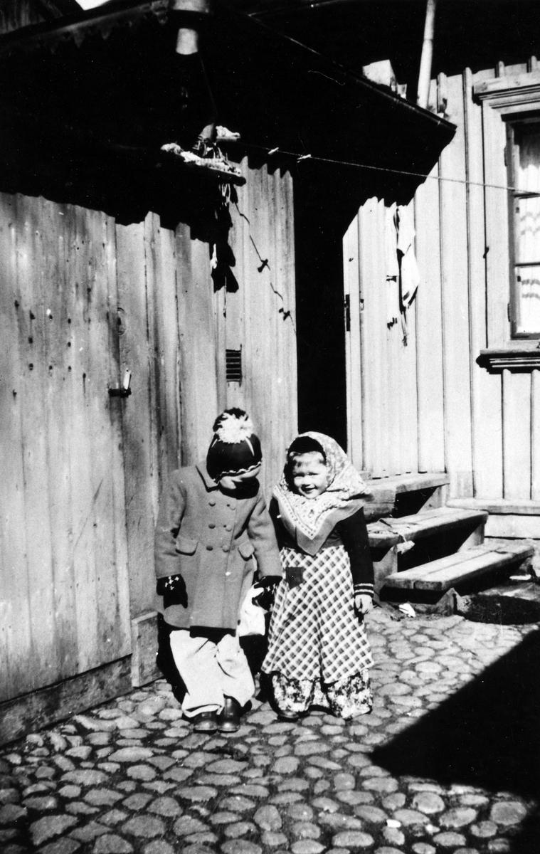 Två stycken påskkärringar står vid en träbeklädd vägg. Till höger: Nils-Arne Sandberg.  Kvarteret Storken, Nygatan 11.