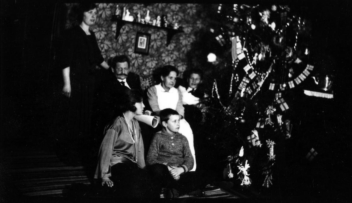 En familj sitter vid sin pyntade julgran, två av barnen sitter på golvet.