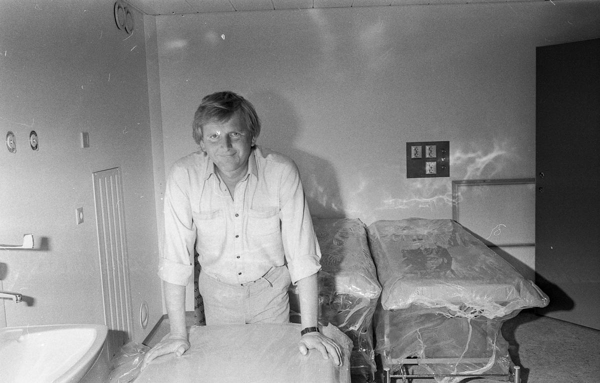 Ring Medisinske Legesenter, rund murbygning. Lege Jens Moe på legekontoret med undersøkelsesbenk, røntgen og diverse medisinsk utstyr.