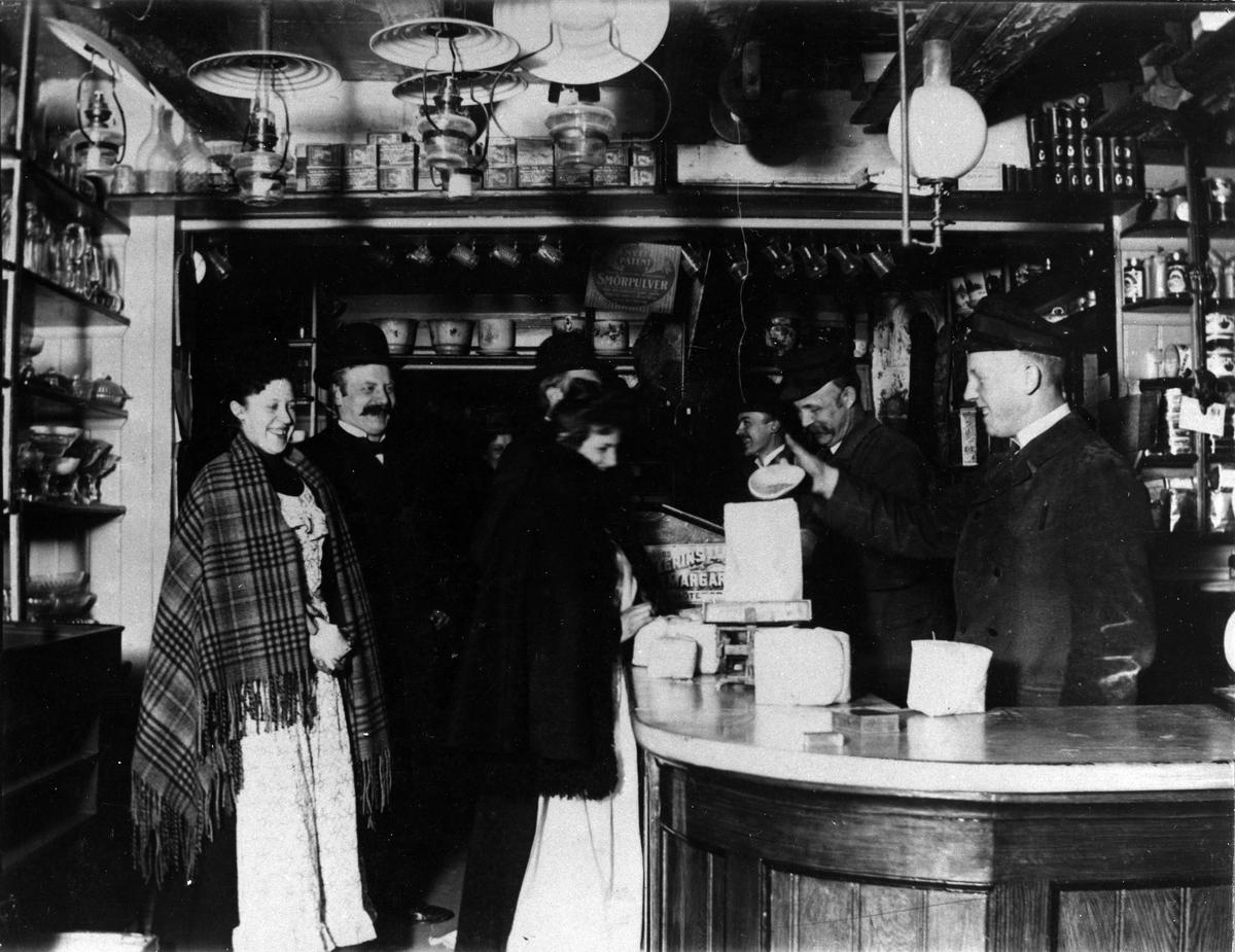 3 män står bakom disken i en speceriaffär och hjälper 2 par kunder. Interiör av Alfred Hedéns affär vid Stora torget.