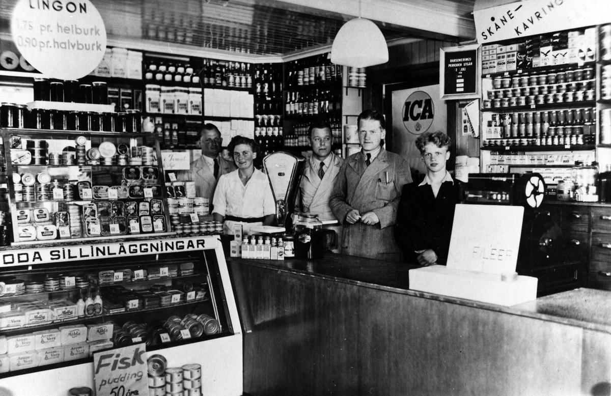 Inifrån Sandbergs speceriaffär. Bakom disken står 3 män, 1 kvinna och 1 tonårspojke. Till vänster en stor glasdisk fylld med olika sillinläggningar. Kvarteret Storken.