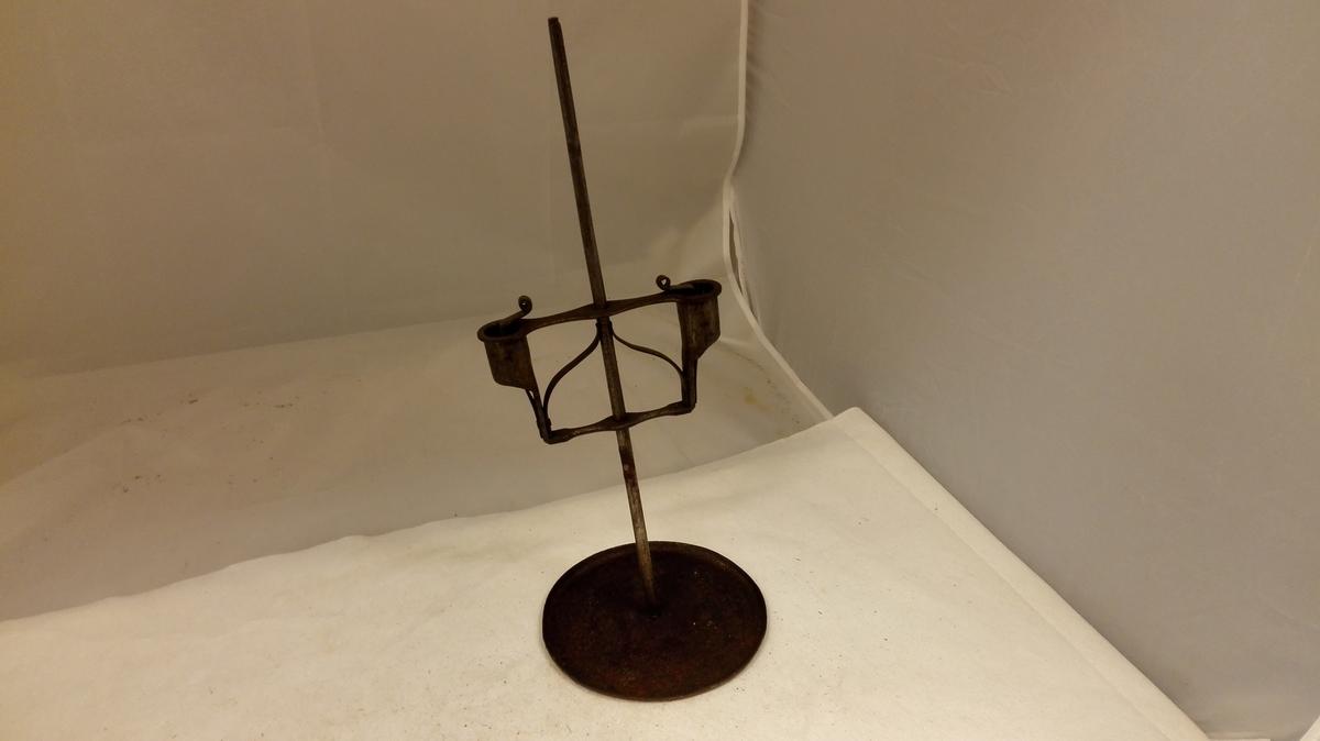 1 toarmet lysestake av jern. En toarmet lysestake (= no 1196), hvis lyseholdere er dreibar og skyvbar paa en gjennem midten gaaende, 39 cm lang, rund jarnten, der er fastsat i fotstykket, en sirkelrund  (diameter 6 cm) jernplate med opoverbøiet kant. I begge lysehul er fjær til at holde lyset. Gave fra gaardbruker Hans Prestegaard, Gaupne.