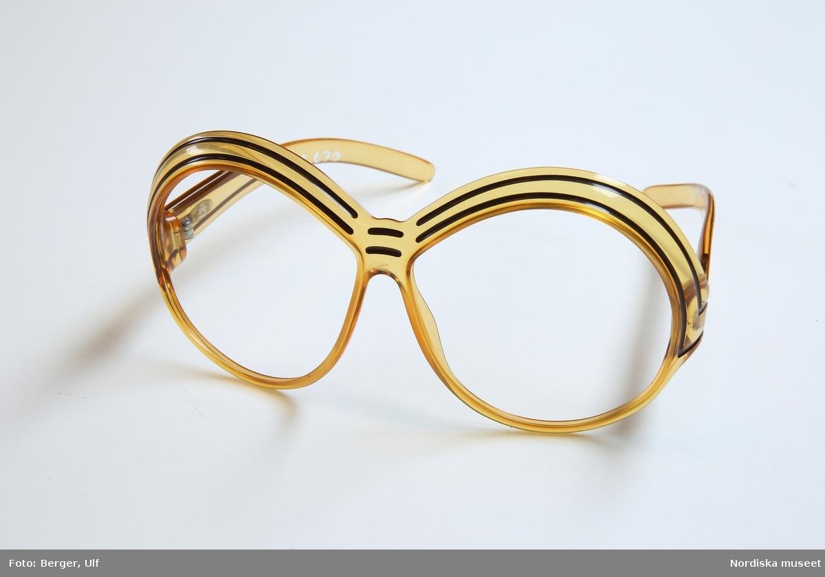 """Solglasögonbågar tillverkade av mörkgul optylplast. Stora, runda bågar med en högt placerad näsbrygga och små inbyggda näskuddar. Två parallella mörkbruna ränder är ingravade på övrekanten och fortsätter ner mot gångjärnen och ut på skalmarna. Metallgångjärn. CD-monogram i guld står på skalmarnas utsidor närmast gångjärnen. På insidan av vänster skalm står """"MADE IN GERMANY 2040-10"""", på insidan av höger skalm står """"optyl (c) Christian Dior"""". """"120"""" är stämplad vertikalt på skalmarnas insidor närmast gångjärnen. /Petrine Knight, 2014-11-05"""
