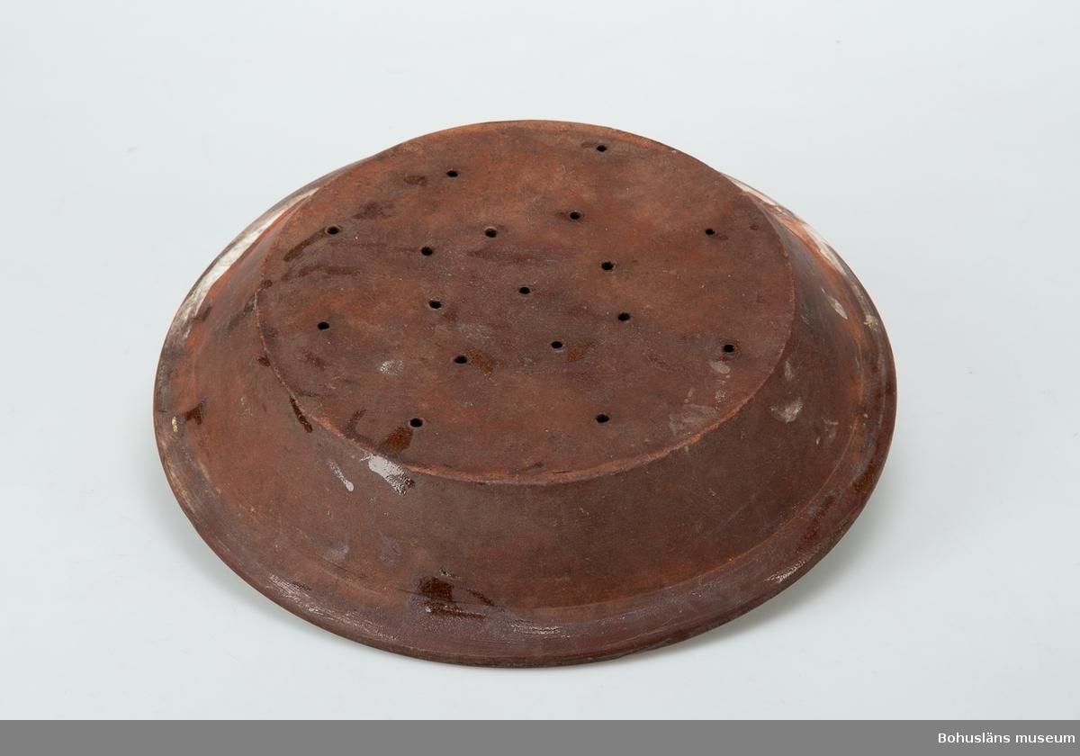 Fat med avrinningsfunktion; 17 hål om 5 mm diameter, radiellt placerade på botten. Gulglaserad insida. Uppåtböjd sida och utvikt bräm, oglaserad ut- och undersida.