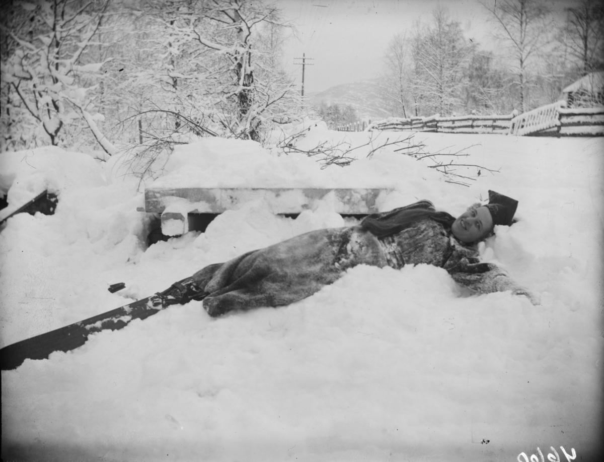 Fru Brun ligger i snø med ski på beina