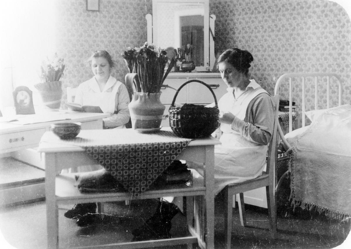 Personalbostad för sjuksköterskor på Alingsås lasarett. Två kvinnor sitter vid var sitt bord.