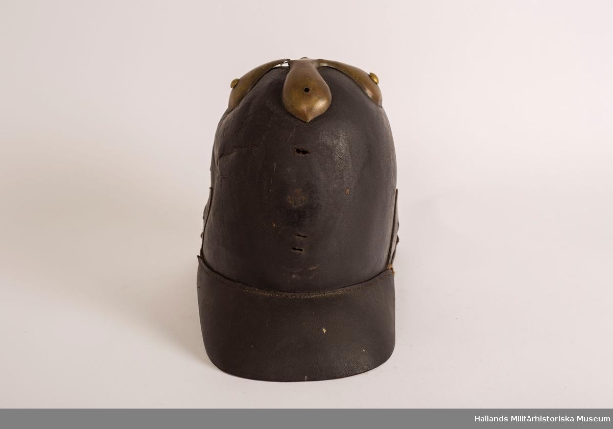 En s.k kask (hjälm) av svart styvt läder. Hjälmen är svagt sluttande upptill med förgylld plåt. Hjälmen har fram- och bakskärm. Förgylld plåt på baksidan som löper lodrätt från toppen av hjälmen ner på bakskärmen. Brunt läder på insidan.