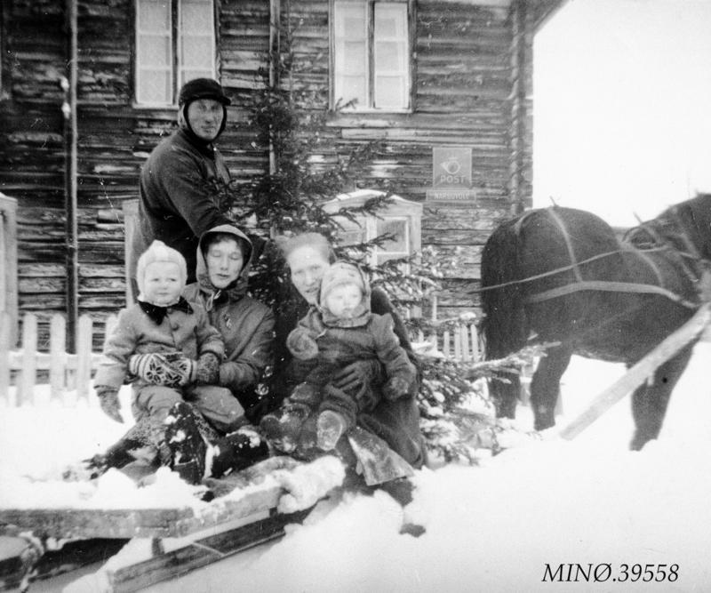 Thomas Engåvoll på Narbuvoll har vært og hentet juletreet.  Oppi slaen sitter Anna Karine og Olga Engåvoll, med Tor Magne og Else Marie, barna på garden. Treet er trulig hentet ved Malmmyra, der det er et plantefelt. Ca. 1960