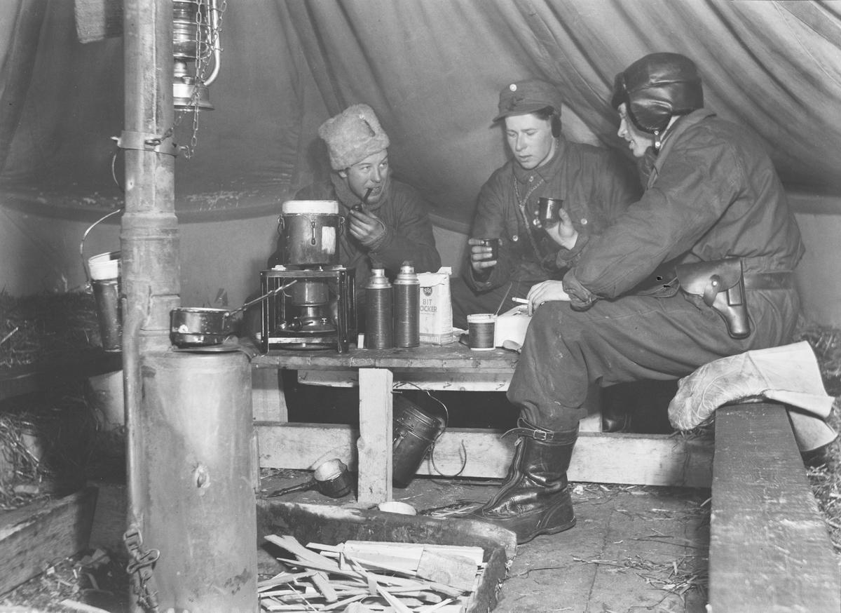 Fikapaus vid Svenska frivilligkåren i Finland, F 19. Tre militärer i tält.