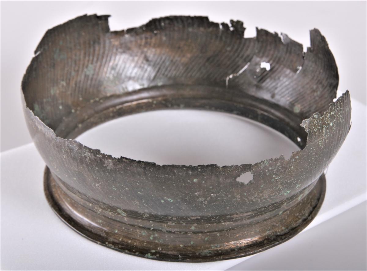 Bronsekjele, som type R. 351, yngre romersk jernalder. En gravurne av bronse i 2 større og 2 små deler (tidligere 3 små deler). Dens nederste bunn og øverste del er hele.  Den har vært utbuet på midten. På bunnens underside er det i midten et lite stempelhull, derpå innrisset to ringer og lenger ut mot kanten to lignende ringer, så kommer en liten avsats som danner en fot til urnen. Fra denne foten vider den seg ut. Urnens øverste del begynner med en brem hvor det innvendig er innrisset to ringer. Utvendig straks nedenfor bremmen en utdrevet fals og nedenfor innrisset 2 ringer. Innvendig i urnen er inntrykket med 1-2 mm. mellomrom streker som begynner oppe ved falsen og synes å ha gått i svinginger ned til bunnen der hvor foten er nedtrykket.