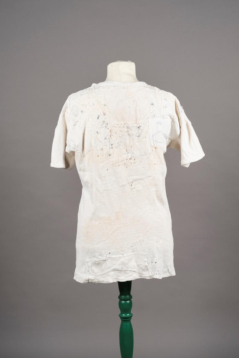 Hvit undertrøye med korte ermer. Det er knepping foran på brystet. med tre knapper. Skjorten er slitt, og det er lappet igjen store hull, ofte med blå tråd. Andre mindre hull er stoppet. Fangenummer er skrevet på under knappene.