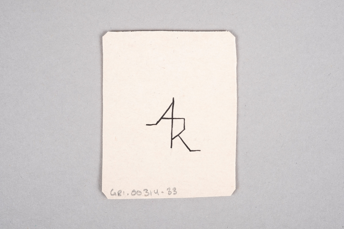 """Håndlaget kort med påført tall og hjertesymbol. På baksiden av kortet er det et monogram av initalene """"AR""""."""