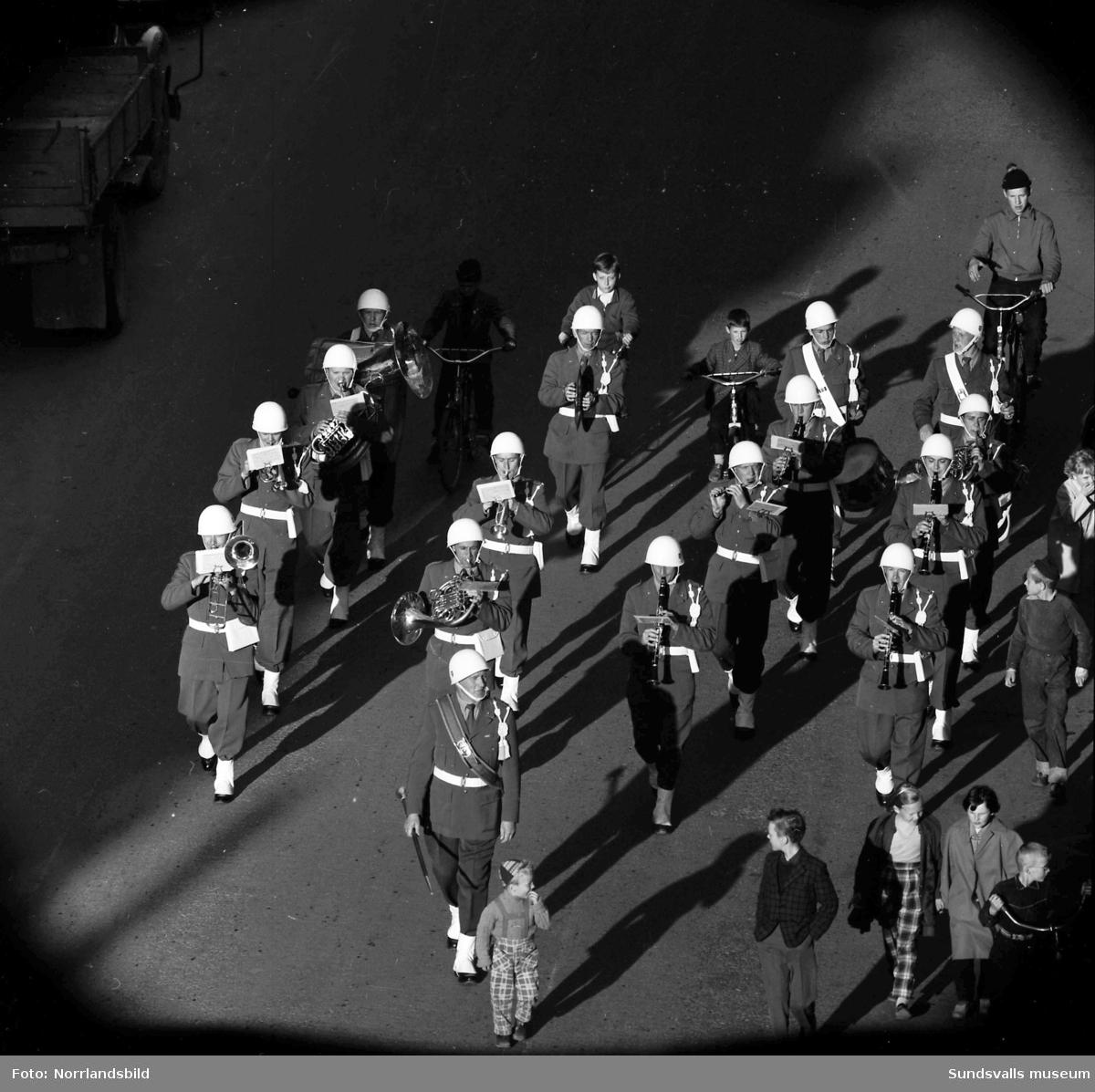 En stor serie bilder från firandet av Svenska flaggans dag 1956. Parad på Storbron med paradorkester, militär, scouter och mängder av olika föreningar och förbund. Därefter högtidlig uppställning i Idrottsparken med bland annat tal, körsång, gymnastikuppvisning och folkmusik.