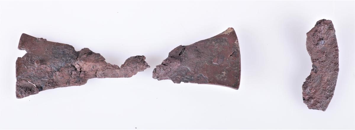 Skjoldhåndtakbeslag i jern fra folkevandringstiden funnet i gravhaug ved Gjerstad gård i 1882. Håndtakbeslag av jern i 2 deler, nærmest R 222 (a og b). a) bredde i enden 6 cm, b) bredde i enden 6 cm. c) et krummet, flatt beslagstykke av jern, lengde 7,5 cm.