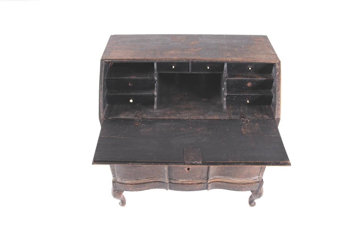 Svartmalt skatoll med buet front. Skatollet er et kombinerte skrive- og oppbevaringsmøbel med tre langskuffer nederst og skrå skriveklaff øverst. Nøkkelhull i hver skuff og skriveklaff.  Skriveklaffen kan brettes ut til et skrivebord ved å dra ut støttene under klaffen. Når skriveklaffen står åpent er der åtte mindre skuffer. Innvendige skuffeknotter er av elfenben. Skatollet hviler på fire S-formede ben.