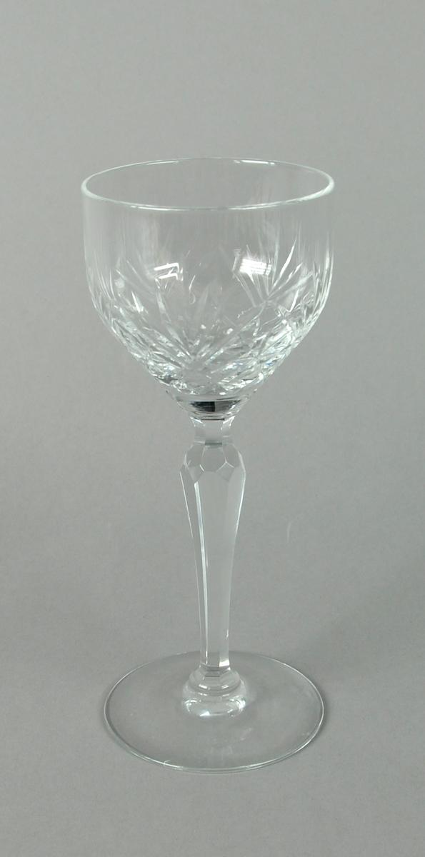 Vinglass av fasettert glass. Glasset har innslipt dekor av palmetter og kryssmønstre. Stetten er fasettert.