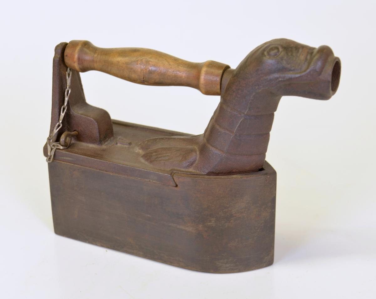Strykjärn av metall med trähandtag. Värmes genom direkt eldning med träkol. Har ursprungligen tillhört den omtalade s.k. Brobackeskräddaren, Brobacken.