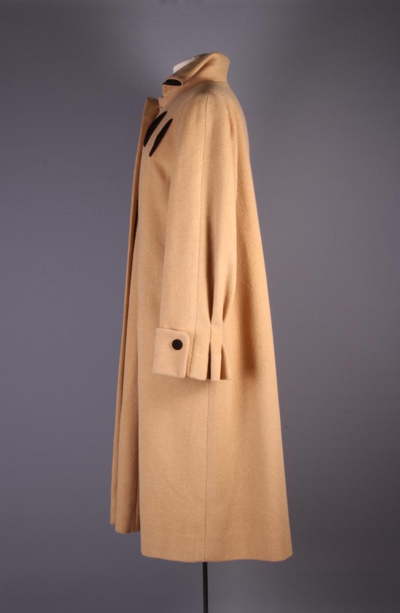 Kåpe i okergult ullstoff med brunt fôr. Detaljer i brun fløyel på knapper, innvendig krage og dekor på frontstykket.
