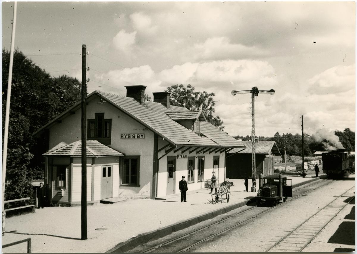 Motordressin står framför stationbyggnad på Ryssby Station.