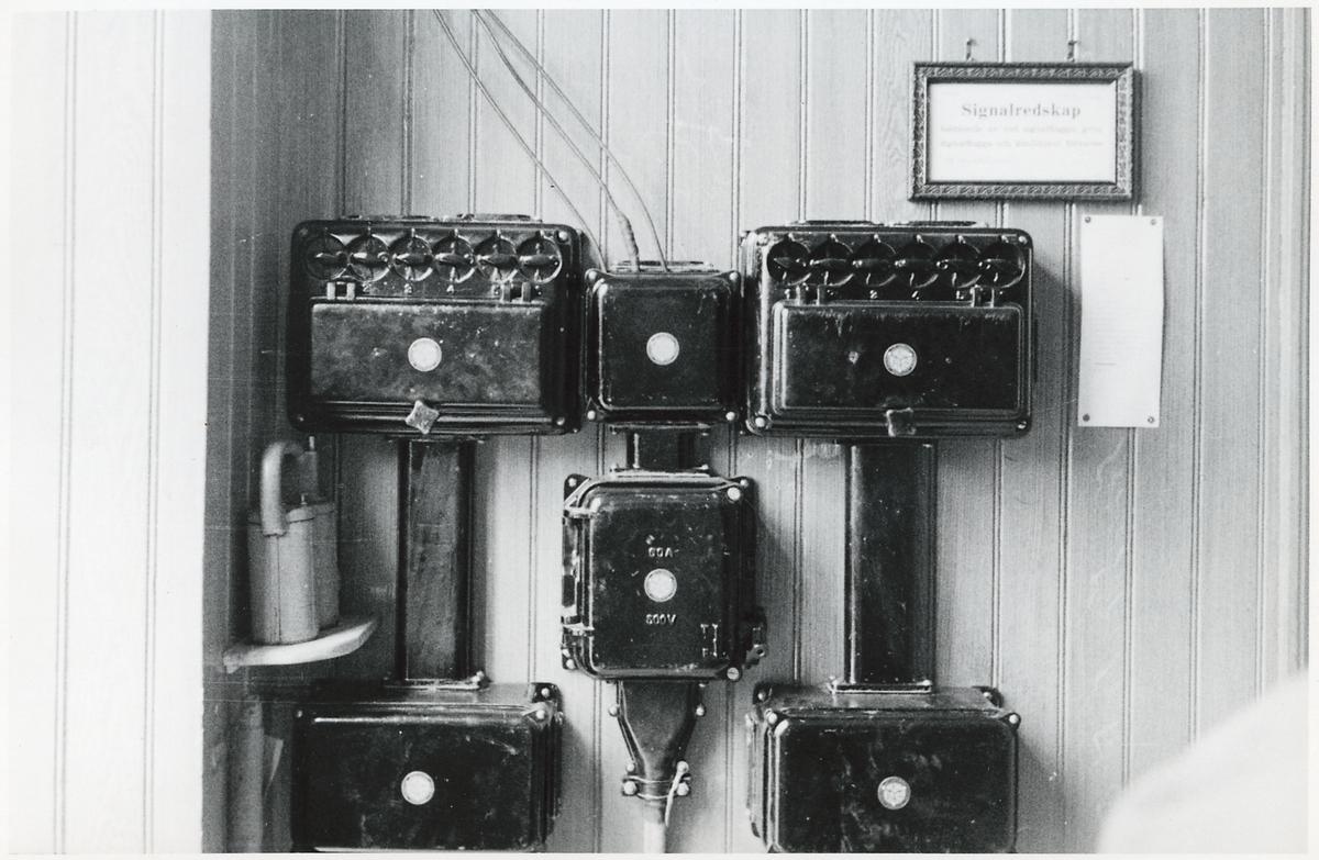 """Elinstallation. Text på skylt: """"Signalredskap bestående av röd signalflagga, grön signalflagga och knalldosor förvaras[...]"""""""