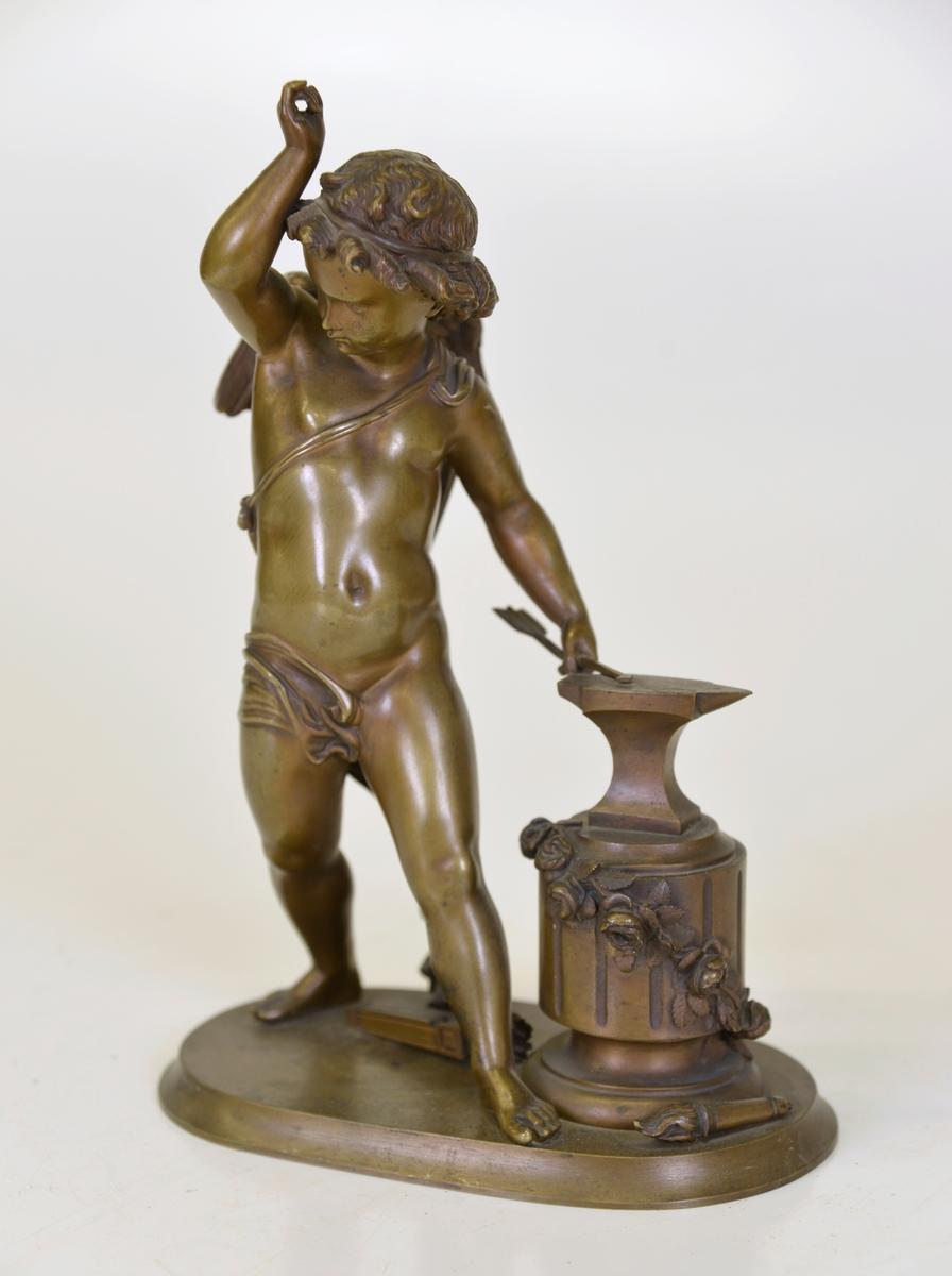 Gjuten brons staty föreställande Amor smidande en pil.