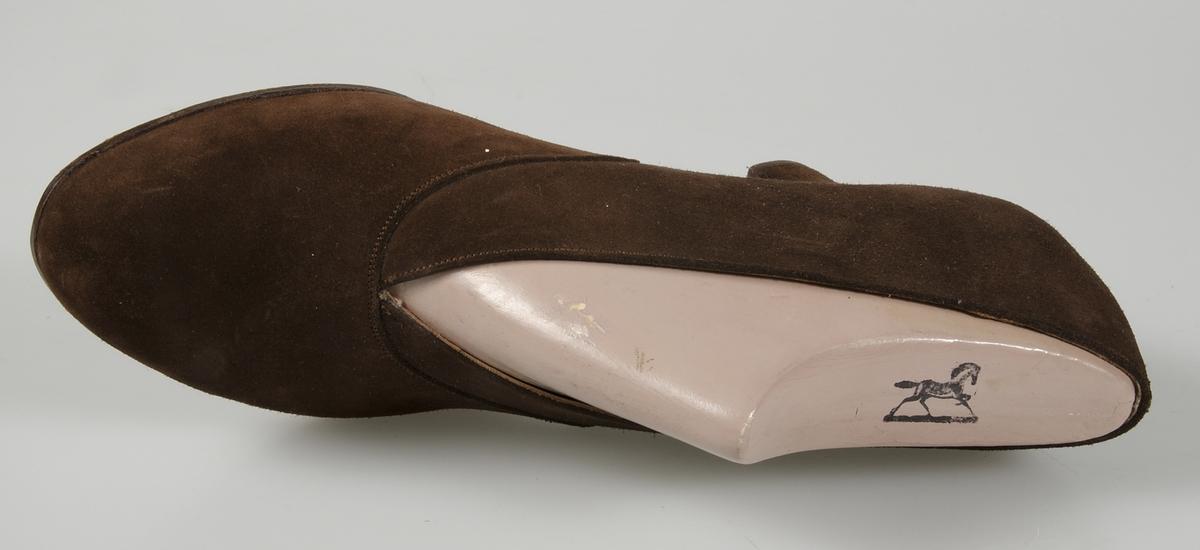 Pumps av brun mocka, spetsig ringnig, mockaklädd klack, lädersula märkt Hästen, märkt med bläck på sulan: 26/1 1949 CE har maken. Storlek 5. Läst av formpressat massamaterial med Hästens fabriksmärke.