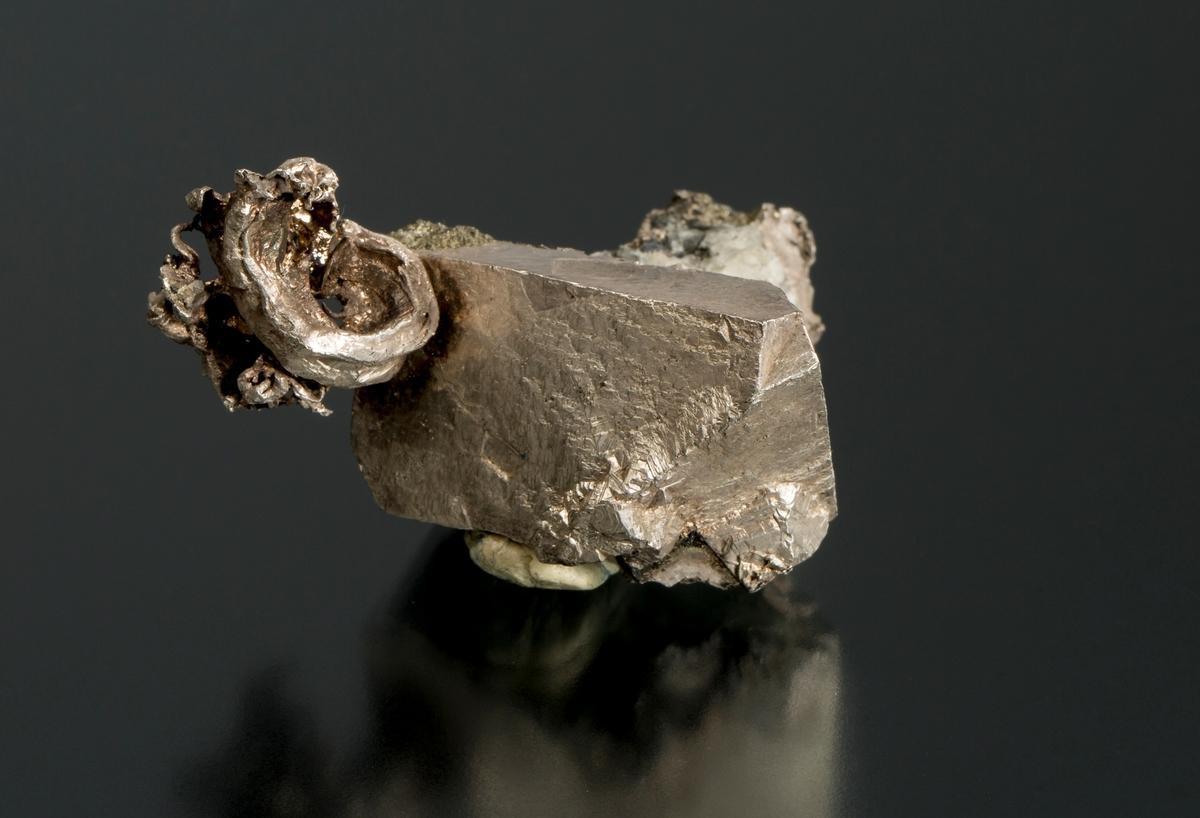 Tvillingkrystall Avbildet i Carl Bugge (1917) Kongsbergfeltets geologi. NGU Nr. 82. Fot. 20. Etikett 18 Vekt 104,47 g Størrelse: 5 x 3,5 x 2,5 cm