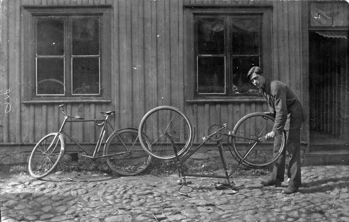 Fritz Johanssons Maskinaffär på Kungsgatan 28 (Nygrens fastighet) i kvarteret Pärlan, Alingsås. Rolf Andersson står här på gården och justerar bakhjulet på en cykel.