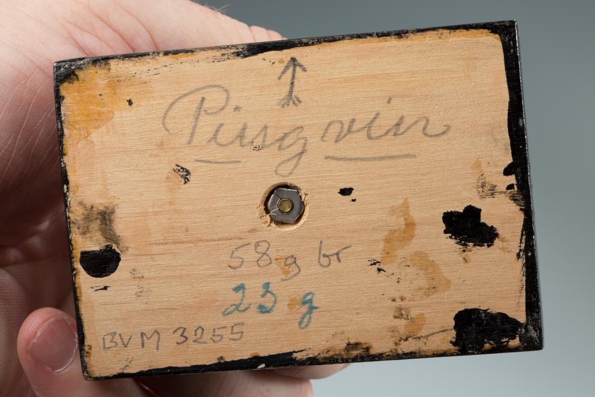 """""""Pingvin"""" på svart plate med påskrift: """"Pingvin, 58 g br, 23 g, BVM 3255"""" Vekt: 58,15 g (med sokkel) Størrelse: 5,3 x 2,7 x 1,2 cm"""