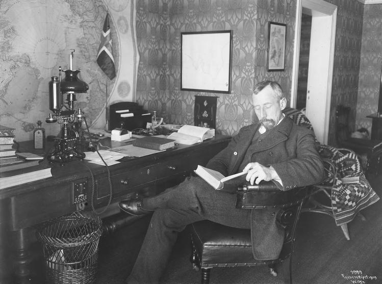 Roald Amundsen sitter og leser på sitt eget kontor i Uranienborg. (Foto/Photo)