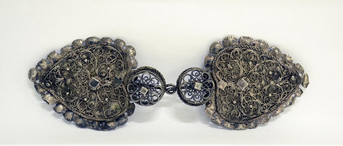 Filigransspenne av sølv, hver del hjerteformet med bole der hekte/hempe er festet.