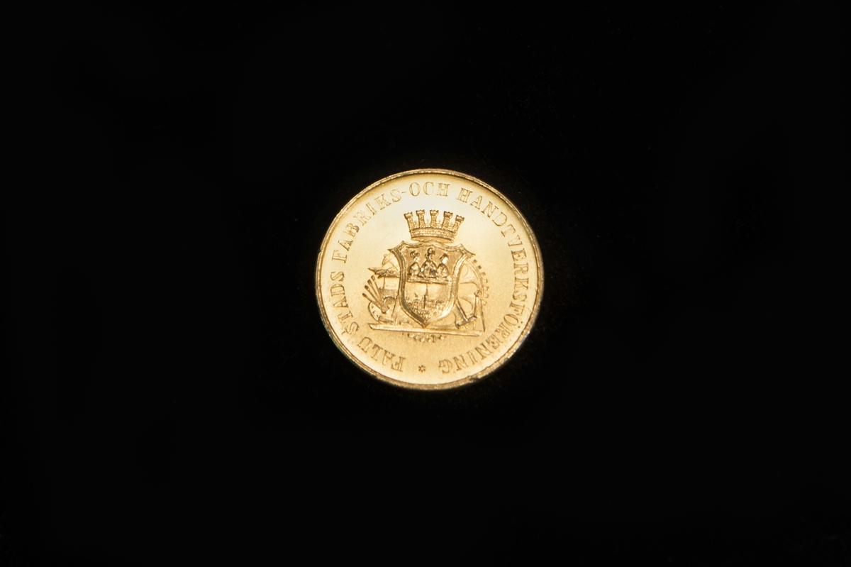 """En medalj av förgylld silver. På åtsidan Falu stadsvapen (äldre) under en krona. Text runtomkring """"Falu stads fabriks- och hantverksförening"""". Frånsidan, texten """"Hantverks- och industriutställningen i Falun 1927"""" och """"A/B John Löfquists skomanufaktur Jönköping"""". Stämplar längst ner. Ligger i en ask av trä, klädd med blågrått papper. Insidan klädd med siden och sammet. Text på insidan av locket C.C. Sporrong & C:o Stockholm."""