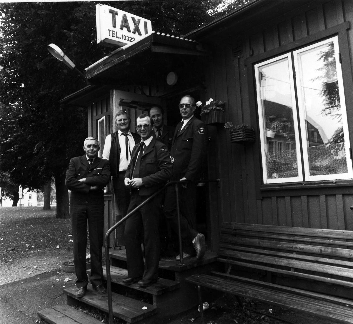 """5 män står på trappan till den gamla taxistationens ingång på Bankgatan i Åmanska parken. Ovanför dom en skylt med text """"Taxi Tel 10322"""". Stationen flyttade i månadsskiftet augusti-september 1982 till nya lokaler i kv. Dryckeshornet."""